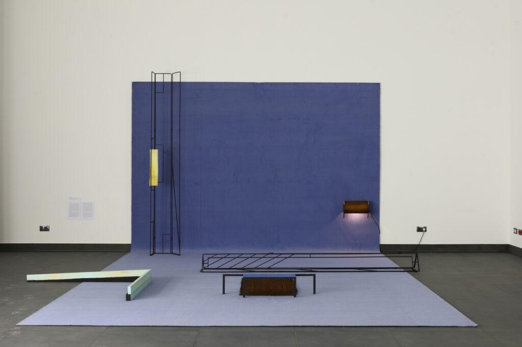 Zdjęcie ukazuje dużą instalację artystyczną składającą się z abstrakcyjnych pod względem kształtu elementów: niebieskiego dywanu położonego na grafitowej podłodze i białej ścianie Sali Wystaw, przypominającego rozpostarte tło fotograficzne, kilku leżących i stojących czarnych metalowych prętów, słupów oraz jednej zapalonej lampy.