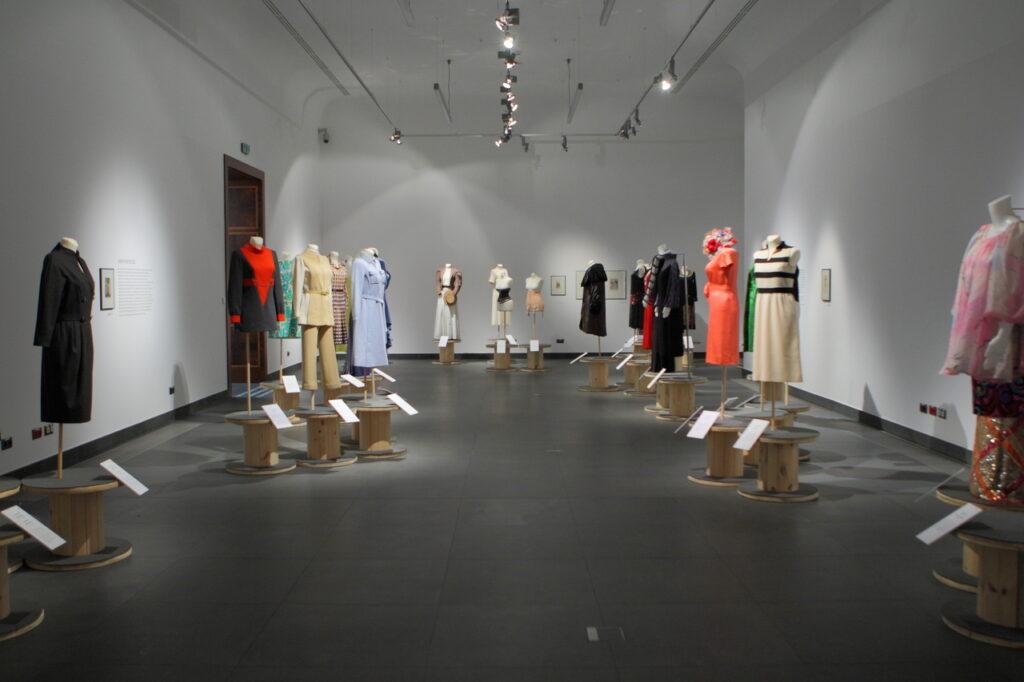 Na zdjęciu widzimy fragment aranżacji wystawy. Na grafitowej podłodze po lewej, jak i po prawej stronie stoi kilkanaście damskich manekinów ubranych w kolorowe suknie, kostiumy, płaszcze i gorsety. Ściany Sali Wystaw pomalowane są na biało. Z lewej strony widoczne są brązowe drzwi, zaś pod sufitem znajdują się liczne reflektory oświetlające ekspozycję.