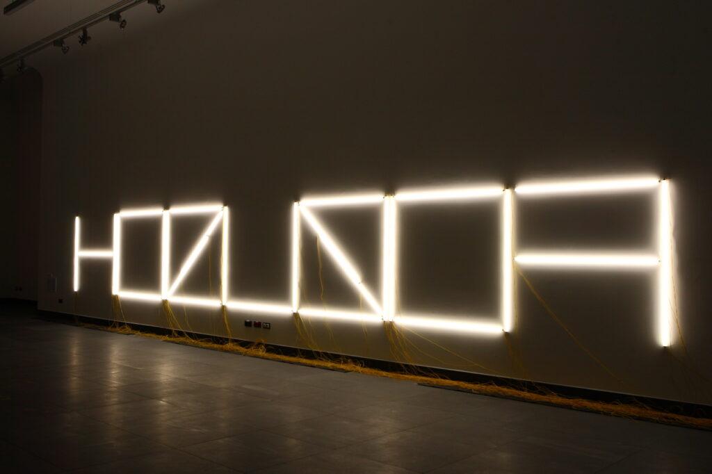 """Głównym motywem zdjęcia jest instalacja świetlna złożona z jarzeniówek, których układ ma sugerować napis: """"hokus fokus"""". Litery są ze sobą połączone, niektóre odwrócone, dlatego napis jest dość trudny do odczytania. Tło jest ciemne, na podłodze dostrzegamy mnóstwo żółtych kabli doprowadzających prąd do neonu."""