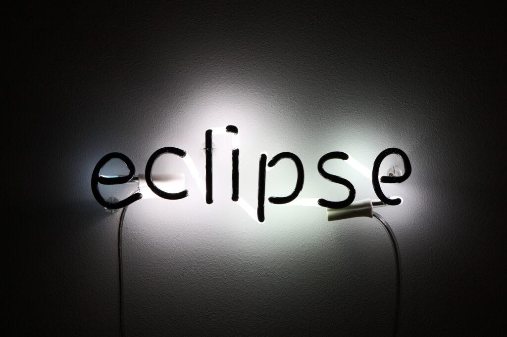 """Głównym motywem zdjęcia jest instalacja świetlna, która tworzy napis: """"eclipse"""". Tło jest ciemne, jedynie centralnie rozświetlone przez neon."""