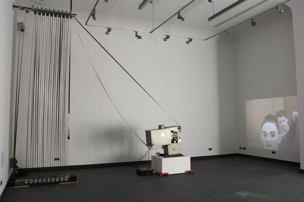 Na zdjęciu widzimy dużą instalację wideo z zatrzymanym kadrem lekcji baletu. Film wyświetlany jest ze starego projektora 35 mm. Taśma filmowa naciągnięta jest na liczne rolki, z których część leży na grafitowej podłodze, a pozostałe znajdują się tuż pod białym sufitem. Pod sufitem zawieszone są również rampy świetlne z reflektorami.