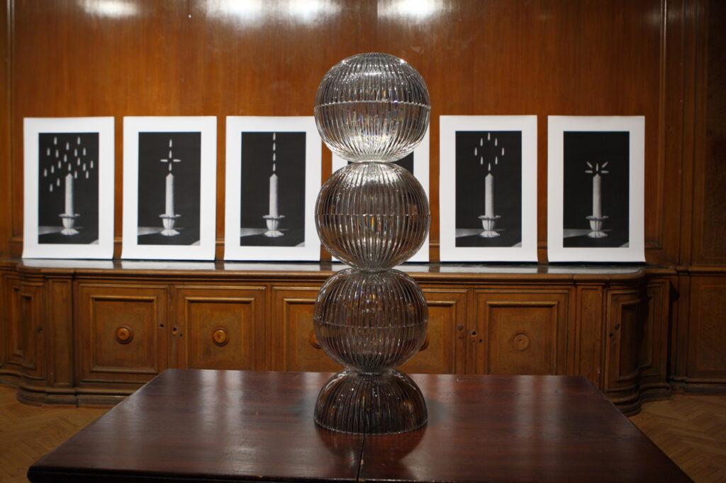Zdjęcie ukazuje instalację artystyczną składająca się z dwóch części. Na pierwszym planie widzimy wieżę utworzoną z półkolistych, kryształowych zamkowych kloszy lamp, stojącą na drewnianym brązowym stole, natomiast w tle – na zabytkowym, również drewnianym kredensie – opartych jest o ścianę sześć czarno-białych fotografii umieszczonych w białych, kartonowych ramach. Tematem zdjęć są pojedyncze świece z wieloma płomieniami układającymi się w różne wzory.