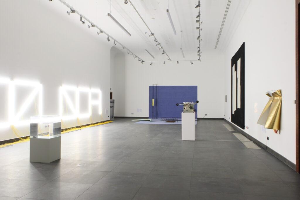 Na zdjęciu widzimy fragment aranżacji wystawy z kilkoma pracami artystycznymi. Są to głównie abstrakcyjne dzieła, instalacje przestrzenne, świetlne, obrazy i tkaniny powieszone na białych ścianach. Podłoga jest grafitowa, a pod sufitem znajdują się rampy świetlne z reflektorami.