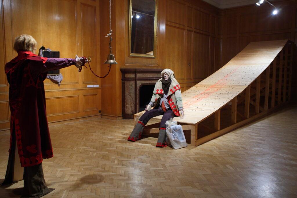 Zdjęcie przedstawia jedną z zamkowych drewnianych sal, w której artysta wykonał instalację przestrzenną składającą się z rampy i siedzącego na nim manekina mężczyzny oraz stojącego naprzeciwko niego drugiego męskiego mężczyzny, ubranego w historyczny strój i trzymającego sznur od dzwonu, który zwiesza się z sufitu. W tle dostrzegamy dwa lustra, jedno duże, jedno małe, w których odbija się światło reflektorów oraz fragment kominka.
