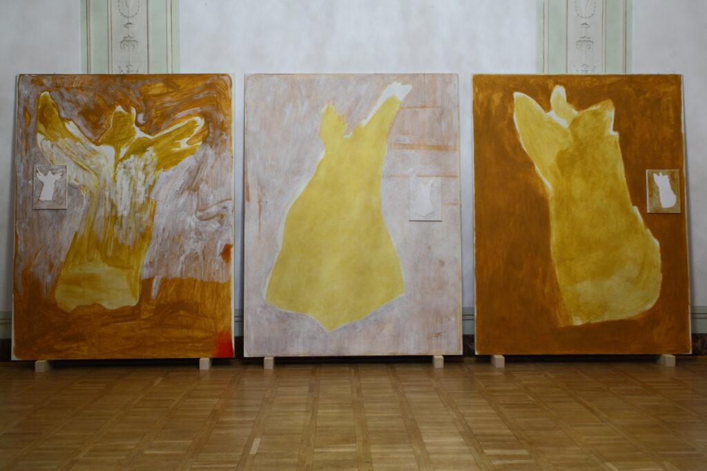 Prawie całą powierzchnię zdjęcia wypełniają trzy duże obrazy olejne na płótnie stojące na drewnianej podłodze, utrzymane w żółto-brązowej kolorystyce i przedstawiające dość abstrakcyjne postaci  przypominające anioły.