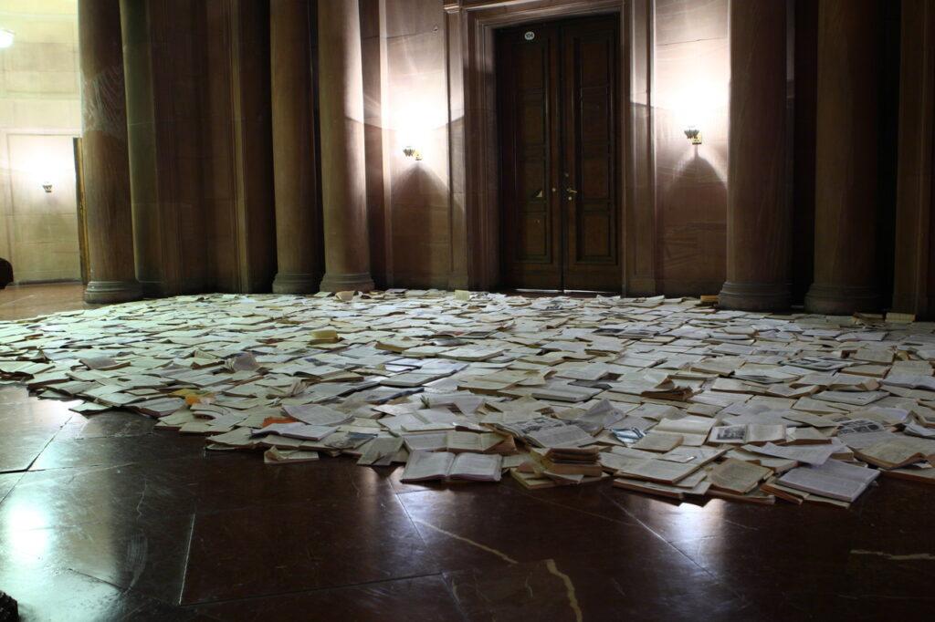 Na marmurowej podłodze, w holu zamkowym leżą setki pootwieranych książek stanowiących instalację artystyczną, po której można chodzić. W tle widzimy fragmenty architektury Zamku: kolumny, duże dwuskrzydłowe drzwi oraz kryształowe kinkiety na ścianach.