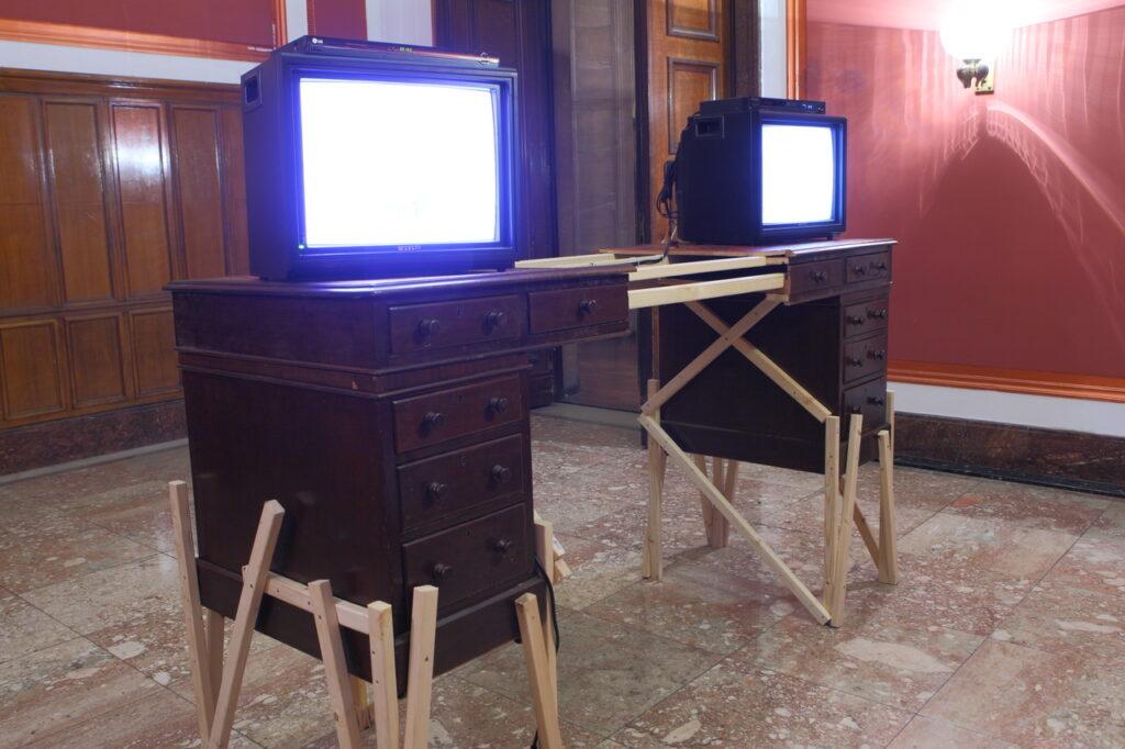 Na zdjęciu widzimy instalację przestrzenną składającą się z przepołowionego starego biurka, którego obie części połączone są cienkimi listewkami. Na blacie stoją dwa włączone telewizory bez obrazu. W tle dostrzegamy fragmenty Sali Kominkowej Zamku: ciemnoczerwoną ścianę z kryształowymi kinkietami, drewnianą ścianę oraz duże drzwi.