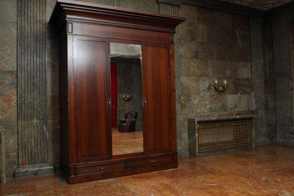 Na zdjęciu widzimy fragment Sali Kominkowej Zamku, w której stoi duża, drewniana, zabytkowa szafa z lustrem, w którym odbija się fotel stojący w oddali. Podłoga oraz ściany są marmurowe.