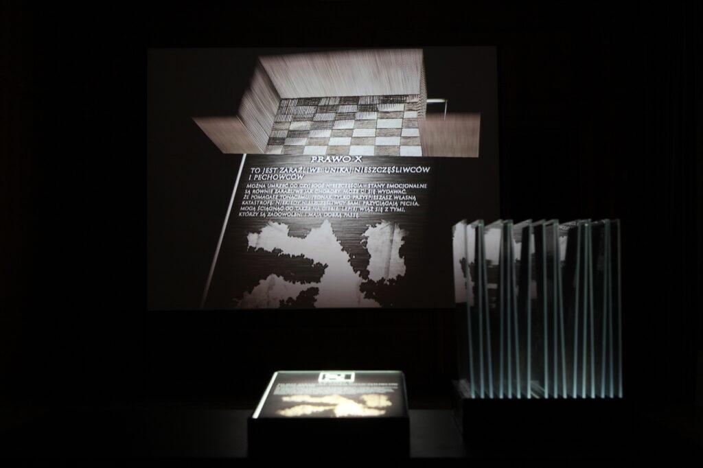 Na zdjęciu widzimy instalację artystyczną składającą się z kilku elementów, które są skonstruowane w taki sposób, że nie do końca jesteśmy w stanie stwierdzić, jaką techniką zostały wykonane. W skład pracy wchodzą: podświetlany postument z grafiką przedstawiającą mapę wraz tekstami, która to grafika dodatkowo odbija się w ciemnej przestrzeni, a obok znajdują się fotografie na szkle.