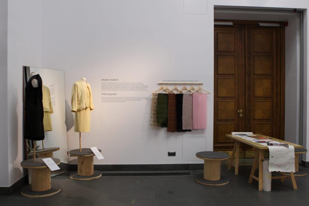 Na zdjęciu widzimy fragment aranżacji wystawy ukazujący pracownię krawiecką. Z lewej strony stoją dwa damskie manekiny i duże lustro, na ścianie na wprost wiszą wieszaki z próbkami tkanin, zaś po stronie prawej znajduje się stół z przyborami do rysowania, magazynami mody oraz rolką papieru. W tle za stołem widzimy duże brązowe drzwi Sali Wystaw.