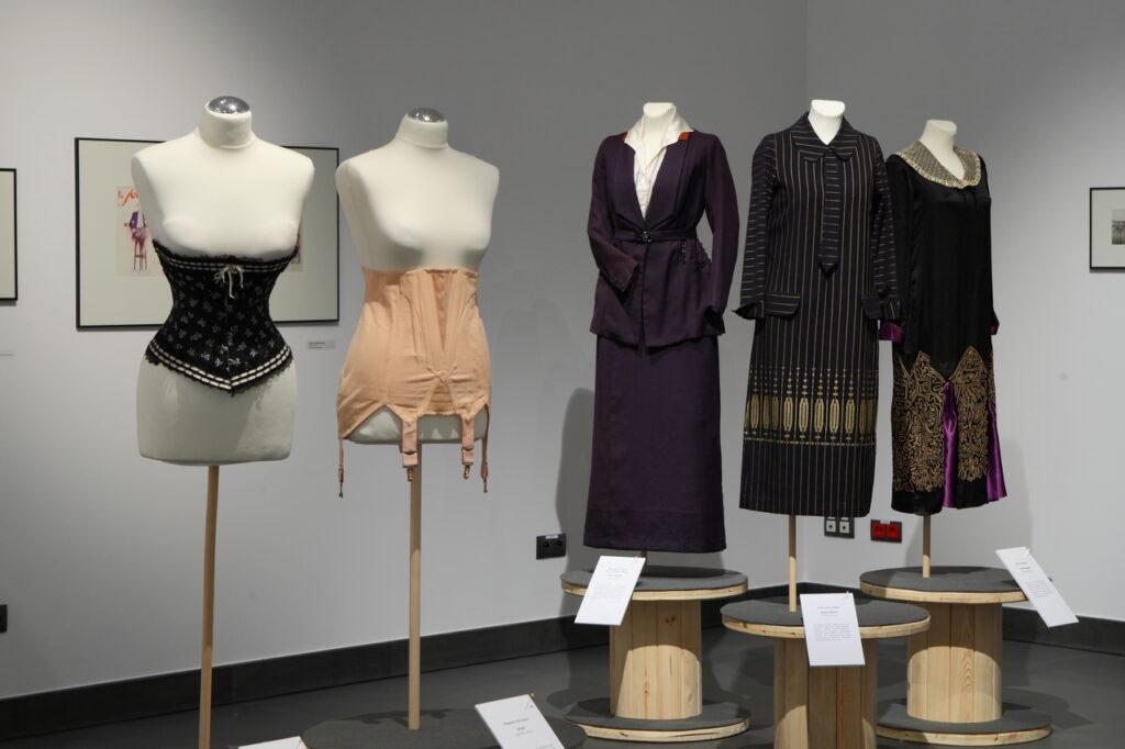 Na zdjęciu widzimy pięć manekinów. Dwa z nich, po lewej stronie, ubrane są w gorsety, trzy kolejne, po prawej, w ciemne suknie z pierwszej połowy XX wieku. W tl, na białych ścianach można dostrzec kilka obrazów z projektami odzieży.