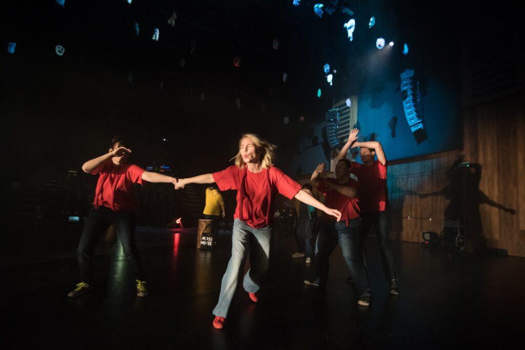 Na zdjęciu centralną postacią jest blondynka ubrana w czerwony t-shirt i błękitne dżinsy. Ma przymknięte oczy i włosy rozwiewające się podczas biegu. Trzyma za rękę drugą kobietę, ubraną w t-shirt tego samego koloru i ciemne spodnie. Jej twarz przysłania druga, wolna dłoń. Po prawej stronie, za kobietami, stoi dwóch mężczyzn w rozkroku, jeden za drugim. Ręce mają uniesione nad głowami. Ta pełna energii scena rozgrywa się na dużej sali z czarną podłogą i boazerią na ścianach. Nad aktorami widać głośniki i inne urządzenia służące do obsługi spektaklu.
