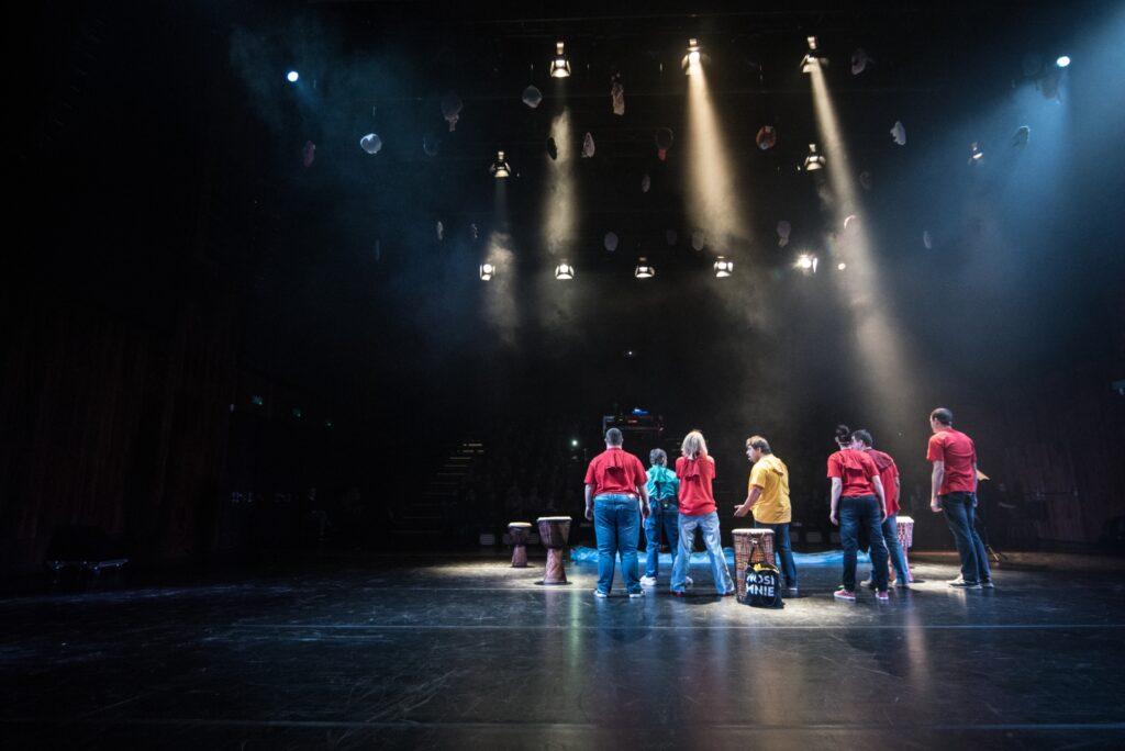 Siedmioro aktorów biorących udział w przedstawieniu ukazanych jest w niecodzienny sposób. Stojący na końcu sceny fotograf uchwycił ich od tyłu, stojących w grupie przed widownią. Ubrani są w kolorowe bluzy i niebieskie spodnie. Na ciemnej połyskującej podłodze oprócz aktorów stoi kilka dużych bębnów. Nad głowami artystów widoczne są smugi światła rzucane przez reflektory zawieszone pod sufitem.