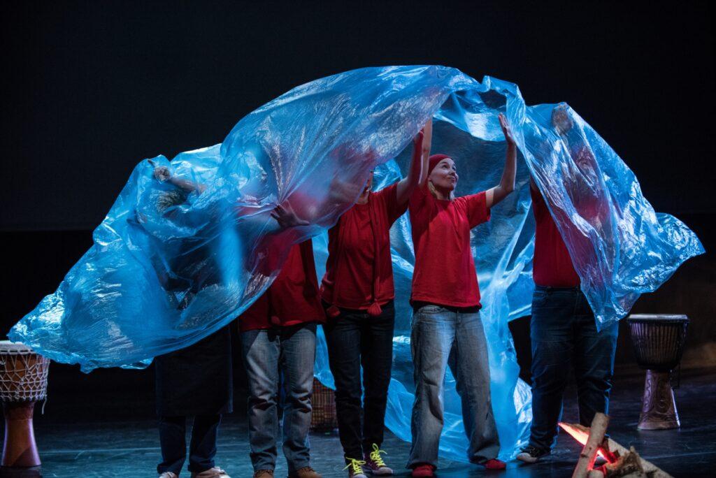Dominującym elementem na fotografii jest niebieska folia wypełniająca niemal połowę obrazu. Trzymają ją nad swoimi głowami aktorki i aktorzy ubrani w czerwone t-shirty. Sylwetka tylko jednej z nich ukazana jest w całości. Twarze pozostałych ukryte są pod folią. Kompozycję zdjęcia uzupełniają dwa duże bębny – rekwizyty ustawione po obu stronach stojącej grupy.