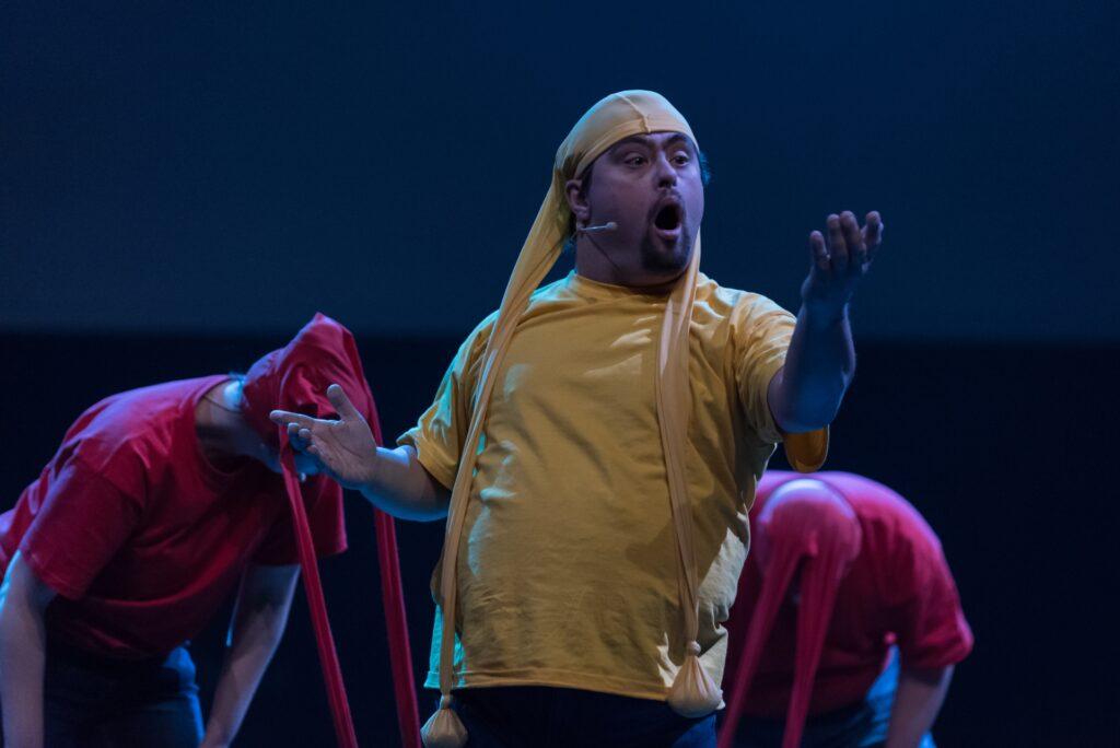 Portret młodego, silnie zbudowanego mężczyzny. Na fotografii dominuje żółty kolor jego kostiumu - koszulki oraz czapeczki wykonanej z rajstop. Osobliwe nakrycie głowy nadaje postaci baśniowego charakteru – zwisające nogawki przypominają długie uszy lub czułki. Aktor uchwycony został w ekspresyjnej pozycji. Jego uniesiona lewa ręka wyciągnięta jest do przodu. Wzrok mężczyzny skupia się na dłoni. Szeroko otwarte, otoczone krótkim zarostem usta są wyrazem zdziwienia lub efektem głośno wypowiadanego tekstu. Na drugim planie fotografii obecne są dwie inne postaci. Ubrane na czerwono stoją pochylone po obu stronach mężczyzny. Ich twarze przysłonięte są opadającymi z głów 'warkoczami' czerwonych rajstop.