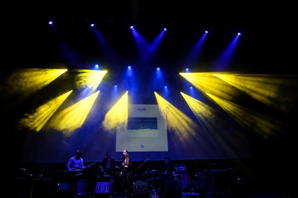 """Zdjęcie przedstawia zespół na scenie oświetlonej niebieskim i żółtym światłem. W tle widoczny jest ekran z grafiką i napisami """"MOLK"""" i """"Tu"""". Z przodu znajdują się członkowie zespołu. Od lewej: basista, gitarzysta, wokalistka, perkusista."""