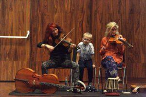 Fotografia przedstawia dwie artystki grające na skrzypcach oraz chłopca. Wszyscy siedzą na krzesłach, na tle pokrytej boazerią ściany. Kobieta po lewej stronie ma długie, bujne, kasztanowo-czerwone włosy. Ubrana jest w czarną bluzkę i ciemne spodnie w jasnopopielate wzory. Trzymanym w prawej dłoni smyczkiem gra na skrzypcach. Na podłodze przed artystką leży wiolonczela. Druga kobieta ma długie blond włosy. Ubrana jest w pomarańczową koszulę i niebieskie spodnie w kolorowe wzory. Trzymany pod brodą instrument strunowy podpiera lewą dłonią. Smyczek, który trzyma w prawej ręce, uniesiony jest w górę, w każdej chwili gotowy do użycia. Pomiędzy skrzypaczkami przysiadł mały chłopiec. Ma krótkie blond włosy i okulary. Ubrany jest w jasnobłękitną koszulę z krótkimi rękawami i ciemne spodnie.
