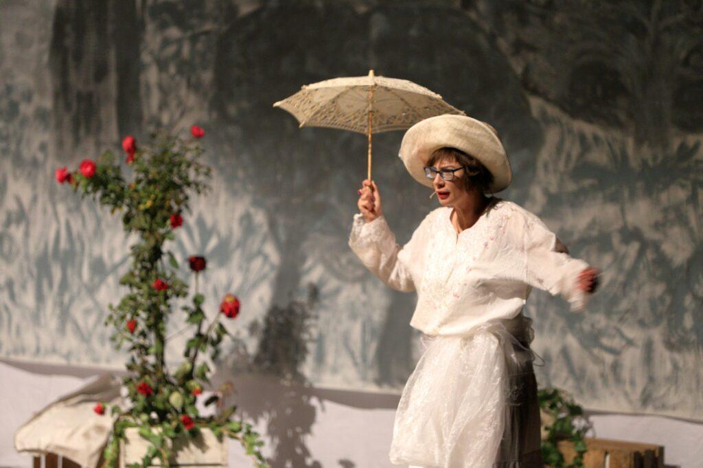 Uchwycona scena przenosi obserwatora do salonu z końca XIX wieku. Sportretowana kobieta jest bardzo elegancko ubrana. Kremowy kapelusz z dużym, wywiniętym rondem i białą koronkową sukienkę uzupełnia delikatna parasolka przeciwsłoneczna. Widoczna z lewego półprofilu postać przemieszcza się po scenie, mówiąc coś jednocześnie do umieszczonego przy twarzy mikroportu. Ma średniej długości kasztanowe włosy, okulary w niebieskiej oprawie i umalowane na czerwono usta. W kompozycji fotografii jej sylwetkę równoważy ustawiony po lewej stronie zielony krzew róży z czerwonymi kwiatami. Rozmazane, utrzymane w szarej tonacji tło dopełnia atmosferę oglądanego obrazu.