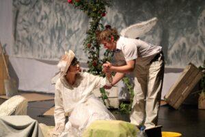 Fotografia przedstawia parę aktorów. Ubrana w białą koronkową suknię i kremowy kapelusz kobieta siedzi na podłodze, co kłóci się z jej wizerunkiem damy. Widzianą z profilu twarz skierowała ku nachylonemu nad nią niskiemu mężczyźnie. Podaje mu z gracją swoją lewą rękę. Młody człowiek ma jasne, lekko potargane włosy. Ubrany w białą koszulę z krótkimi rękawami i jasne spodnie uśmiecha się do kobiety. Przypięte do pleców skrzydła pozwalają domyślać się, że w spektaklu odgrywa rolę anioła. Po prawej stronie zdjęcia, u dołu, widać drewnianą skrzynkę ogrodniczą. Z kolei po drugiej stronie stoi oparty o kolejną skrzynkę szpadel. Ogrodową scenografię dopełnia krzew róży pnącej się za aktorami.
