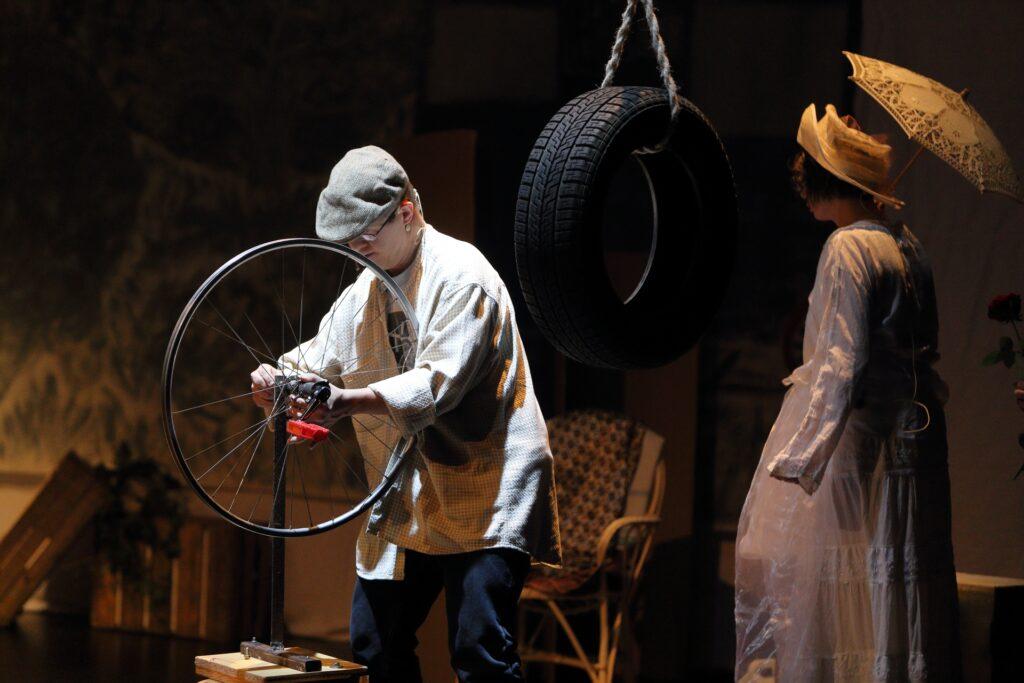 Uchwycona na zdjęciu scena przedstawia wnętrze zakładu mechanicznego. Centralna postać, młody człowiek ubrany w czapkę, jasną flanelową koszulę i ciemnoniebieskie spodnie, stoi pochylony nad rowerowym kołem. Połączona srebrnymi szprychami felga osadzona jest na metalowym stojaku. Ułożone na środku koła dłonie mężczyzny coś przykręcają. Druga postać, kobieta w jasnej koronkowej sukni i kremowym kapeluszu, stoi obrócona tyłem. Nad głową trzyma parasolkę przeciwsłoneczną, w kolorze kapelusza. Pomiędzy postaciami, na pierwszym planie, wisi nowa, czarna opona samochodowa. Pozostałe elementy scenografii to wiklinowy fotel i ustawione w lewym dolnym rogu dwie drewniane skrzynki ogrodnicze.
