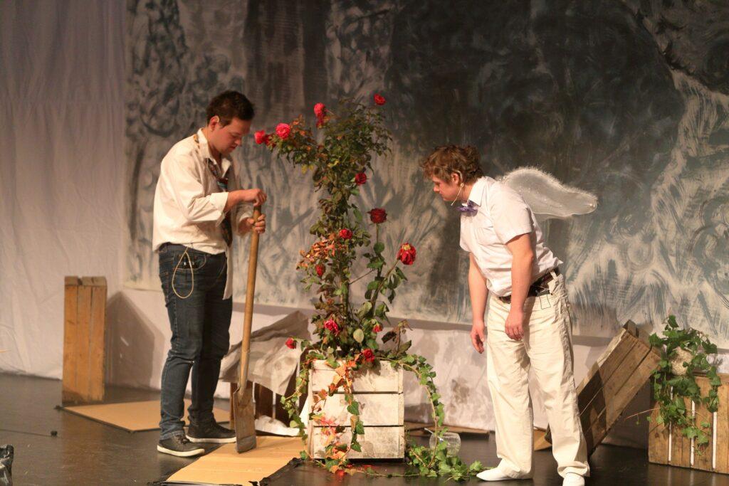 Na fotografii widzimy sylwetki dwóch aktorów. Stoją po przeciwległych stronach zielonego krzewu pnącej róży o czerwonych kwiatach. Krzew osadzony jest w dużej, pomalowanej na biało drewnianej skrzyni. Młody mężczyzna po lewej ubrany jest w białą koszulę i ciemne dżinsy. Z szyi zwisa mu niedbale zawiązany kolorowy krawat. Spogląda na własne dłonie ułożone na trzonku ogrodowego szpadla. Drugi, pochylony do przodu mężczyzna, swoją uwagę skoncentrował na krzewie róży. Ubrany jest w białą koszulę z krótkimi rękawami i jasne spodnie, pod szyją ma zamocowaną fioletową muszkę, a na plecach białe anielskie skrzydła. Tło obrazu stanowi materia w szare plamy, a kompozycję całości uzupełniają trzy drewniane skrzynki ogrodnicze.