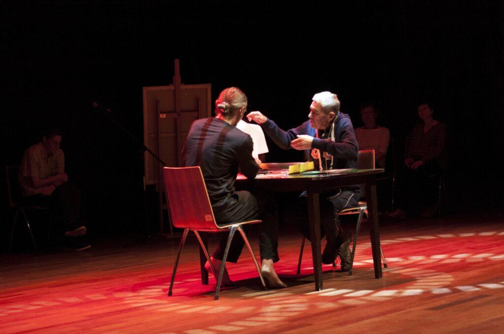 Dwóch mężczyzn siedzi naprzeciw siebie przy czarnym stole. Mężczyzna w starszym wieku zwrócony jest przodem do osoby oglądającej fotografię. Ma siwe włosy i jest ubrany w dres. Wzrok i dwie uniesione ręce zwrócił w kierunku kartki, którą trzyma drugi mężczyzna, zwrócony do oglądającego plecami. Długie włosy ma związane z tyłu głowy. Ubrany jest w czarne spodnie i ciemny t-shirt. Siedzi boso. Na podłodze widoczne są kręgi rzucane przez sceniczne światła. Drugi plan tworzy odwrócona tyłem do widza sztaluga. Po obu jej stronach widać zarysy postaci przysłuchujących się rozmowie dwóch mężczyzn.