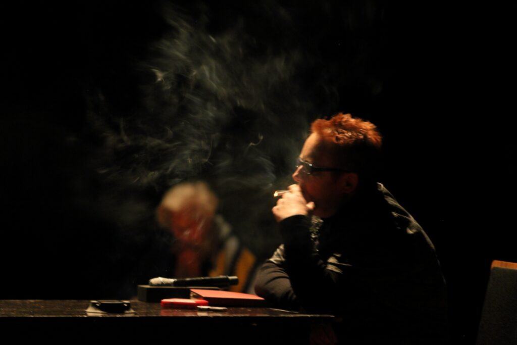 Kobieta w średnim wieku siedzi bokiem – widzimy jej lewy profil i górną część tułowia. Ma krótkie rude włosy i okulary w ciemnej oprawie. Zaciąga się trzymanym w lewej dłoni papierosem. Jest zamyślona. Dym unosi się nad ciemnym, połyskującym blatem stołu, na którym oparła ręce. Przed nią leży kilka przedmiotów: mikrofon sceniczny, popielniczka, czerwony notatnik i pomarańczowe pudełko odbijające światło. Na drugim planie widać bardzo niewyraźny zarys innej postaci.