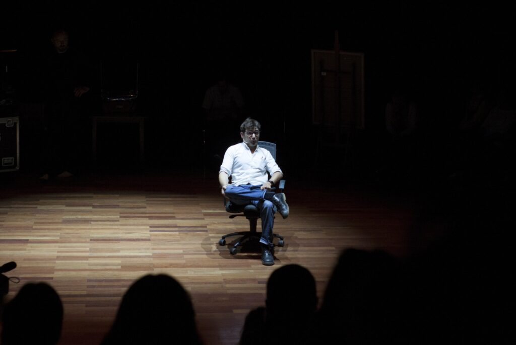 Młody mężczyzna siedzi na obrotowym fotelu w centrum sceny. Na parkiecie zaznacza się krąg światła teatralnego reflektora. Postać ma ciemne włosy i okulary. Mężczyzna ubrany jest w białą koszulę z podwiniętymi rękawami i niebieskie dżinsy. Prawą nogę założył nonszalancko pod kątem prostym na lewej. Przy prawym uchu zamocowany ma mikroport, do którego mówi coś w stronę publiczności. Jej obecność zaznaczona jest u dołu zdjęcia ciemnymi zarysami głów. Są pogrążone w mroku podobnie jak tło całego obrazu.