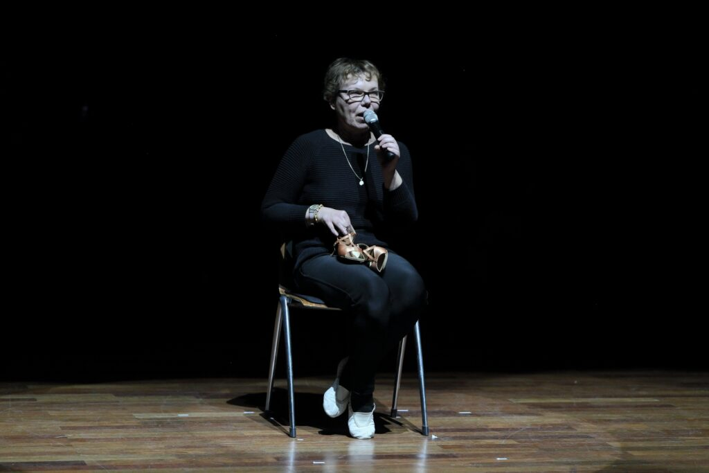 Fotografia przedstawia kobietę siedzącą na krześle. Ma krótkie włosy i okulary. Ubrana jest w sweter i spodnie w kolorze granatowym. Na ciemnym tle wyraźnie zarysowuje się zawieszony na jej szyi złoty wisiorek, a na przegubie prawej ręki bransoletka i zegarek. Kobieta mówi do mikrofonu trzymanego w lewej dłoni. Można się domyślić, że tematem opowieści są wyeksponowane, leżące na jej kolanach złote pantofle. Wyglądają jakby pochodziły z innej rzeczywistości. Tło obrazu jest czarne, odcięte linią scenicznych świateł.