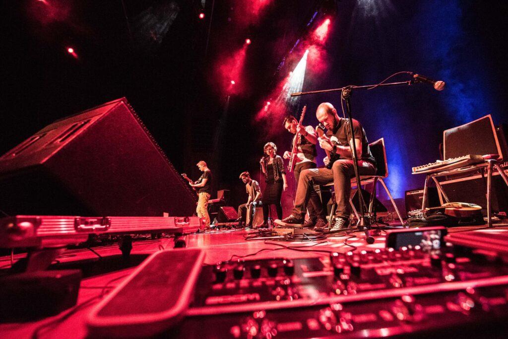 Zdjęcie zrobiono z boku sceny, z poziomu jej podłogi. Na pierwszym planie znajdują się nożny przełącznik gitarowy oraz elementy nagłośnienia. Za nimi – członkowie zespołu: gitarzysta, basista, wokalistka, bębniarz i basista. Scena oświetlona jest czerwonymi światłami z delikatną niebieską poświatą padającą zza muzyków.