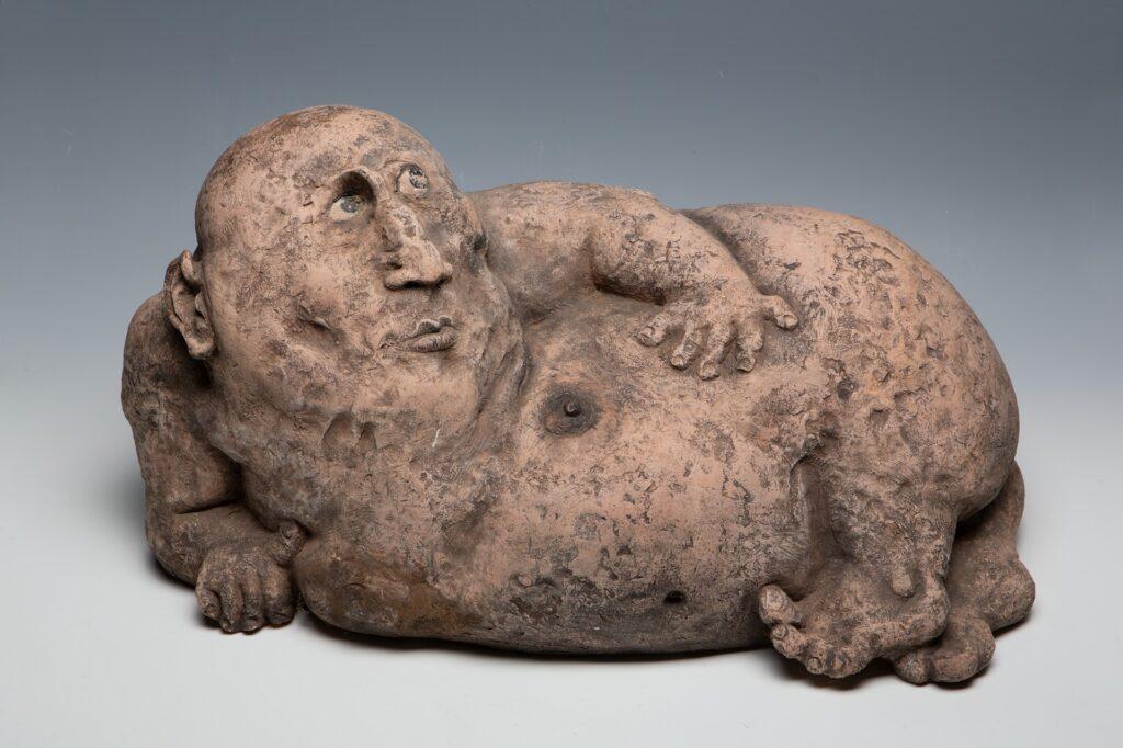 Na zdjęciu widzimy ceramiczną rzeźbę w kolorze jasnego brązu przedstawiającą karykaturalnie otyłą, leżącą na prawym boku i podpierającą się ręką, nagą postać mężczyzny. Głowa postaci jest stosunkowo duża, zaś ręce i nogi nieproporcjonalnie krótkie. Wzrok mężczyzny skierowany jest ku górze.