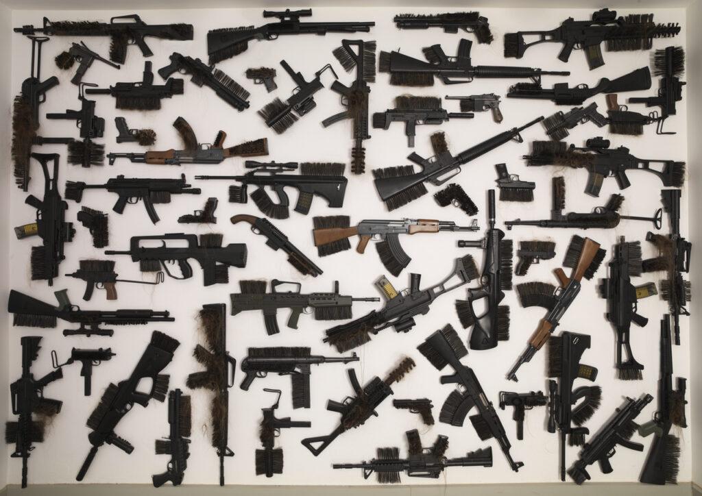 Na fotografii widać kompozycję złożoną z wielu czarnych pistoletów, rewolwerów, karabinów przerobionych na szczotki i pokrytych włosami. Tło jest białe, a całość tworzy abstrakcyjną formę.