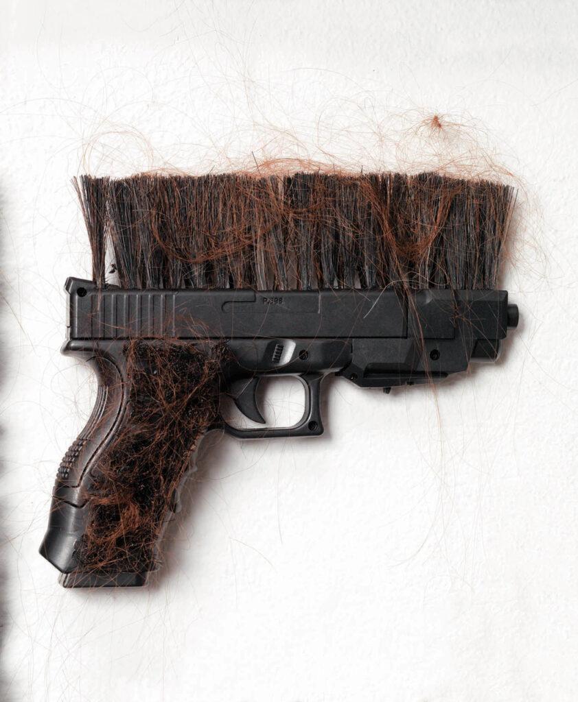 Na fotografii widać czarny pistolet. Na górnej, lufowej części broni przymocowano czarne, szczeciniaste włosie, które przypomina szczotkę oraz wiele luźno zaczepionych, jakby niedawno wyczesanych rudych włosów. Do magazynku pistoletu przyklejone są również rude włosy. Tło pracy jest białe.
