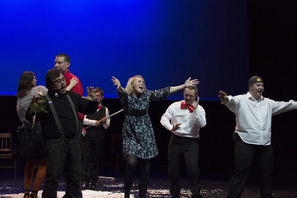Grupowe zdjęcie pokazuje siedmioro aktorów biorących udział w spektaklu. Wszyscy tańczą. Widoczna w centrum obrazu blondynka ekspresyjnie rozkłada skierowane do przodu ręce. Śpiewa, przechyliwszy głowę w lewą stronę. Dwaj mężczyźni po prawej, ubrani w białe koszule i ciemne spodnie, również tańczą. Jeden ma zawiązaną pod szyją dużą czerwoną muchę w białe grochy, a drugi – nałożoną na głowę czapkę bez daszka. Czworo aktorów po lewej stronie fotografii widzimy ustawionych w trzech planach. Tańczący najbliżej mężczyzna ma czarną koszulę i ciemne spodnie na szelkach. W prawej dłoni trzyma różę. Za jego plecami znajduje się tańcząca para – wysoki młody mężczyzna w czerwonej koszuli i ubrana w szary, wełniany sweter, kobieta. Na ostatnim planie elegancki młody człowiek przygląda się tańczącym, trzymając w rękach miotłę.