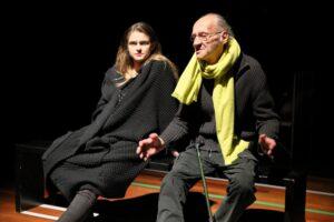 Zdjęcie przedstawia parę aktorów siedzących na prostej, czarnej ławce. Młoda kobieta po lewej jest ubrana w zapinany z przodu, długi, ciemny wełniany sweter i spodnie. Ma długie, jasne, opadające na ramiona włosy i usta pomalowane czerwoną szminką. Odchylona lekko do tyłu oparła się obiema rękoma o skraj ławki. Zmrużyła oczy, wsłuchując się w to, co mówi mężczyzna. Jest to starszy człowiek z łysiną zakończoną rzadkimi siwiejącymi włosami i okularami w drucianej oprawie. Ubrany jest w zapinany na zamek błyskawiczny, ciemny wełniany sweter i ciemne spodnie z kieszeniami na przedzie nogawek. Jego szyja owinięta jest dużym żółtym szalem, który stanowi jedyny kolorowy akcent na fotografii. Wypowiadane słowa wzmacnia gestem szeroko rozłożonych i nisko trzymanych rąk. O prawe udo oparł laskę w zielonkawym kolorze. Postaci przedstawione są na czarnym tle. Jedynie u dołu obrazu widać jasny pas parkietu, na który naklejone zostały białe i zielone linie.