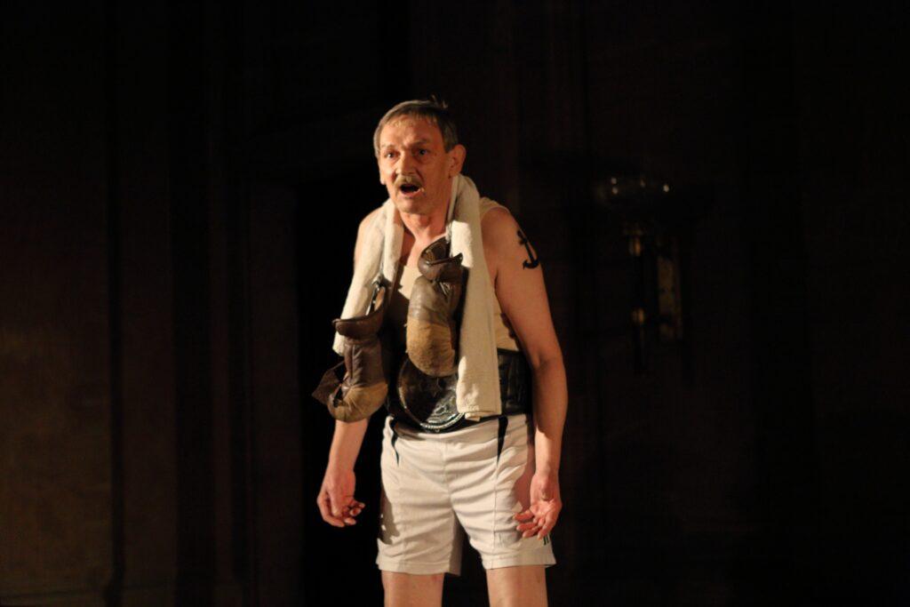 Fotografia jest portretem mężczyzny biorącego udział w spektaklu. Ukazany jest od wysokości kolan w górę. Ma szpakowate, uczesane z przedziałkiem włosy i wąsy. Patrzy wprost przed siebie. Ma otwarte usta. Na prawym ramieniu widać wyraźnie tatuaż w kształcie czarnej kotwicy. Teatralny kostium aktora nie budzi wątpliwości, jaką postać odgrywa w spektaklu. Jest bokserem ubranym w biały podkoszulek na cienkich ramiączkach i krótkie sportowe spodenki. Wokół szyi zawieszony ma również biały ręcznik i bokserskie rękawice, a w talii szeroki skórzany pas z ogromną, metalową klamrą. Tło na zdjęciu jest ciemne i pozwala dostrzec jedynie pojedyncze, niewyraźne detale zabytkowej przestrzeni, w której sfotografowano aktora.