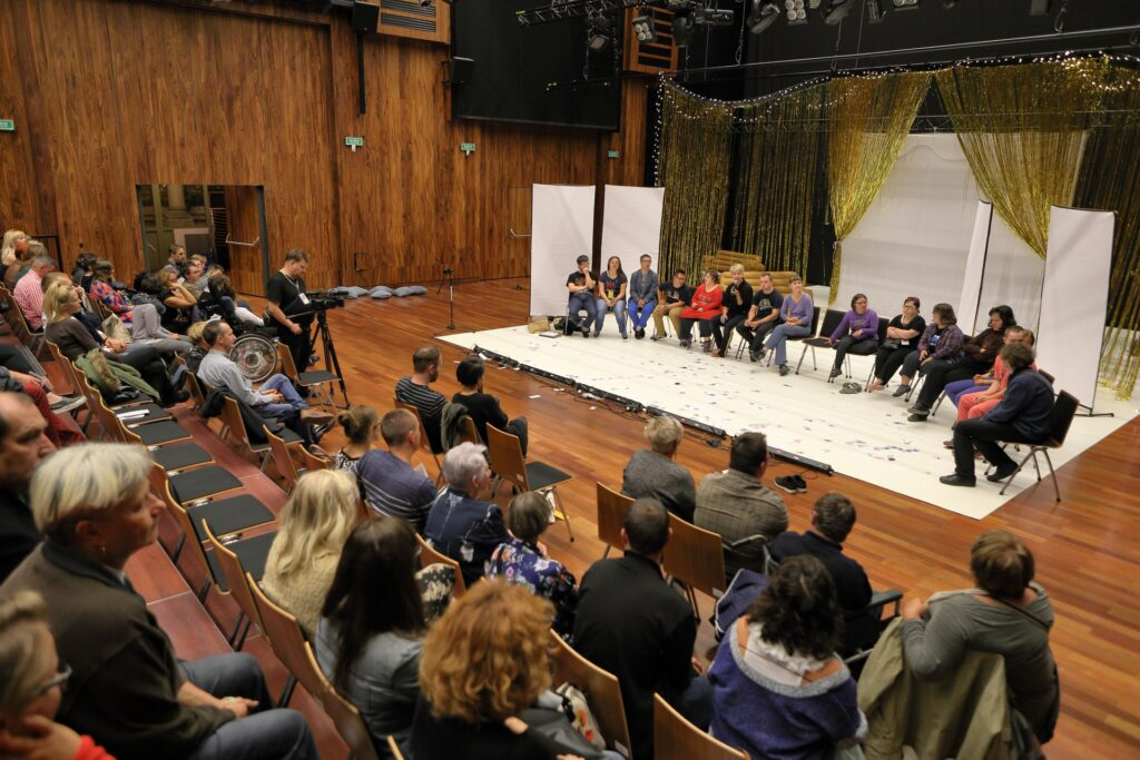 """Widok na scenę z boku jednego z pierwszych rzędów amfiteatralnej widowni. Pole gry wyznacza prostokąt białej materii ułożonej na drewnianej podłodze Sali Wielkiej. Na ustawionych w półokręgu krzesłach siedzi kilkanaście osób. Znajdują się na tyle daleko od obiektywu, że trudno dostrzec szczegóły ich ubioru czy mimiki. Za ich plecami rozstawiona została scenografia spektaklu """"Upadki"""" składająca się m.in. z białych, prostokątnych ścianek i kotary zwieszającej się kaskadą złotych nitek. Na pierwszym planie fotografii znajdują się pierwsze rzędy krzeseł, na których siedzą liczni uczestnicy spotkania."""