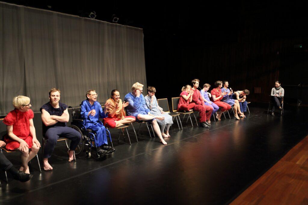 Czarna, pusta scena. Kilkanaście postaci siedzi na ustawionych w rzędzie krzesłach, jeden mężczyzna siedzi na wózku. Większość artystów ubrana jest w niebieskie lub czerwone kostiumy. Wszyscy z czegoś się śmieją, a dwie osoby biją nawet brawo. Po dokładnym przyjrzeniu się fotografii można zauważyć, że źródłem tego rozbawienia jest prawdopodobnie wypowiedź mężczyzny siedzącego po prawej stronie, daleko od obiektywu. Trzyma on mikrofon blisko twarzy i promiennie się uśmiecha. W spowitej ciemnością głębi sceny, za aktorami, zawieszona jest biała kotara z delikatnej tkaniny.