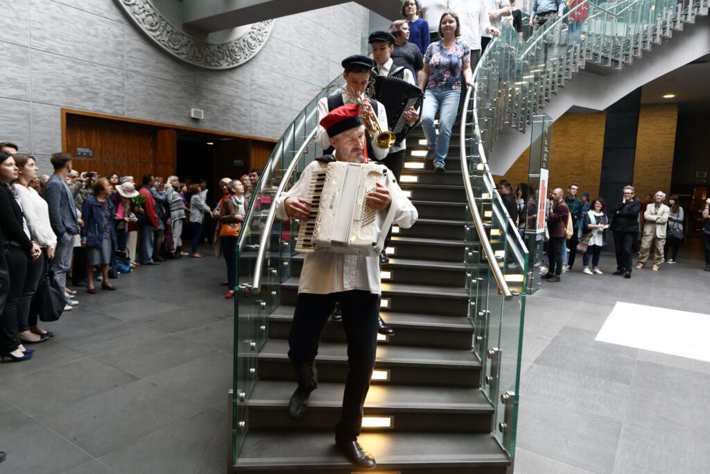 Zdjęcie przedstawia pierwszą scenę spektaklu. Biorący w nim udział artyści idą w dół schodami. Na pierwszym planie muzyk grający na akordeonie ubrany jest w ciemne spodnie, białą koszulę i czerwoną czapkę krakowską z pawim piórem. Ma siwy zarost. Za nim idą inni dwaj muzykanci, młodsi, ubrani w białe koszule, ciemne kamizelki i czapki maciejówki. Pierwszy z nich gra na trąbce, drugi na akordeonie. Za orkiestrą podążają aktorzy. Wszyscy są uważnie obserwowani przez kilkudziesięcioosobową publiczność. Tworzy ona półokrąg ciągnący się od lewej strony fotografii ku prawej, przerwany przebiegającymi centralnie schodami. Po lewej stronie otwarte drzwi do Sali Wielkiej pozwalają domyślać się kierunku, w którym zmierza korowód artystów.