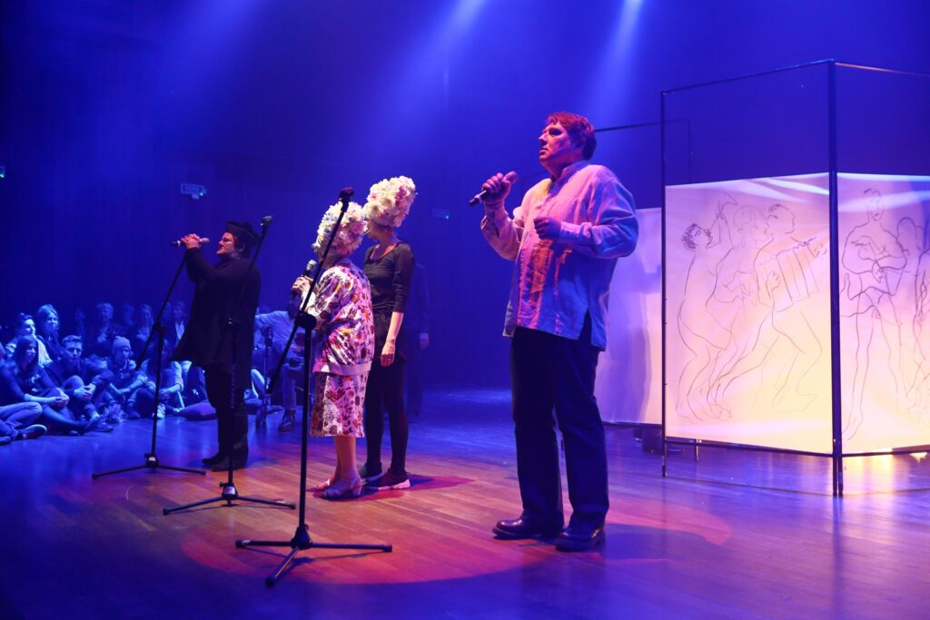 Zdjęcie ukazuje sposób funkcjonowania scenografii spektaklu i relację z publicznością, której część widzimy po lewej stronie. Wpatrzeni uważnie w aktorów widzowie siedzą na odległym planie, na podłodze. Ukazani są w niebieskiej poświacie. Na parkiecie oświetlonym reflektorem stoją cztery postaci. Najbliżej znajduje się mężczyzna w białej koszuli i ciemnych spodniach, trzymający w prawej ręce mikrofon zdjęty ze statywu. Za statywem stoją dwie kobiety odwrócone tyłem. Na głowach mają wysokie, ozdobne czepki weselne. Niższa, ubrana w kolorowy kostium również trzyma mikrofon. Wraz z drugą kobietą, ubraną na ciemno obserwują czwartą postać. To kobieta w okularach przebrana za księdza. Uniesionymi do góry dłońmi obejmuje swój, spoczywający na statywie, mikrofon.