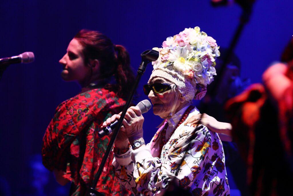 Zdjęcie jest portretem dwóch aktorek. Stojąca bliżej, starsza, ma na sobie kolorowe jasne okrycie i kwietny, wysoki weselny czepek, zawiązany pod szyją. Na twarzy okulary w ciemnej oprawie, a na przegubie lewej ręki zegarek. W dłoniach trzyma uniesiony do wysokości ust mikrofon, zdjęty ze statywu dzielącego fotografię na dwie części. Zamazana postać za starszą kobietą położyła na jej lewym ramieniu rękę. Ma zaczesane do góry kasztanowe włosy, związane z tyłu w tzw. koński ogon. Na ramiona zarzuciła kolorową chustę, w której dominuje czerwień. Zaciśnięte usta, widoczne z profilu jej twarzy, są oznaką skoncentrowania podczas rozgrywającej się sceny spektaklu.
