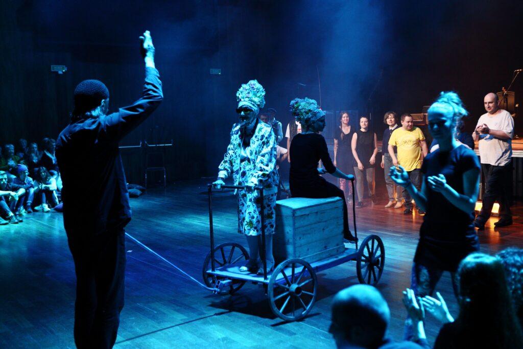 Fotografia przedstawia jedną z ostatnich scen spektaklu, gdy aktorzy, tworząc ponownie barwny korowód, opuszczają Salę Wielką. Mężczyzna stojący tyłem po lewej stronie uniesioną prawą ręką dyryguje pozostałymi postaciami. Centralne miejsce na zdjęciu zajmuje wózek z dyszlem, na którym postawiono drewnianą skrzynię. Przed skrzynią stoi starsza kobieta w okularach, ubrana w kolorowy strój z ozdobnym, wysokim czepkiem. Dłonie oparła na metalowej ramie usytuowanej z przodu wózka. Po drugiej stronie, na skrzyni, przysiadła druga, ubrana na ciemno kobieta, na głowie której widzimy taki sam kolorowy, weselny czepek. Pozostali aktorzy widziani na drugim planie ustawiają się gęsiego, gotowi do wyruszenia w drogę.