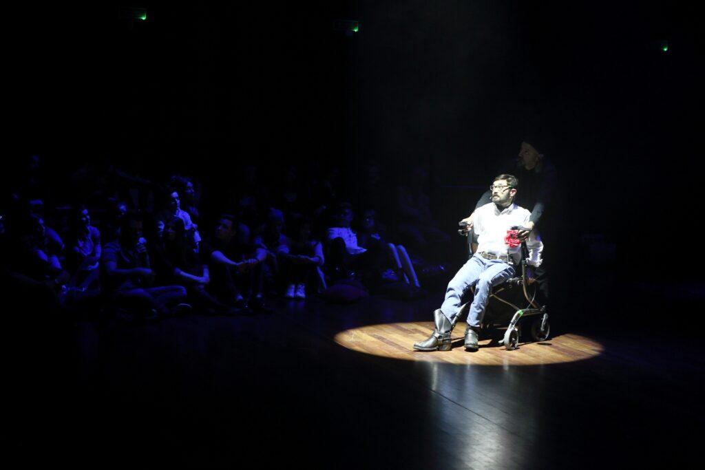 Zdjęcie ukazuje jednocześnie scenę spektaklu i usytuowanie części publiczności. Ukryci w mroku widzowie siedzą na podłodze. Ich ukazane w niebieskim świetle sylwetki są ledwo dostrzegalne. Centralną postacią fotografii jest aktor mocno oświetlony teatralnym reflektorem. Ubrany w białą koszulę, dżinsy i kowbojskie buty siedzi na chodziku, jakim posługują się osoby z niepełnosprawnością ruchową. Ma ciemne, krótko przycięte włosy, brodę i wąsy. Jego wzrok zza okularów skierowany jest ponad głowami publiczności. Podobnie jak widownia, słabo widoczna w mroku jest stojąca za aktorem postać. Wyraźnie zarysowane są jedynie jej oparte na uchwytach chodzika dłonie.