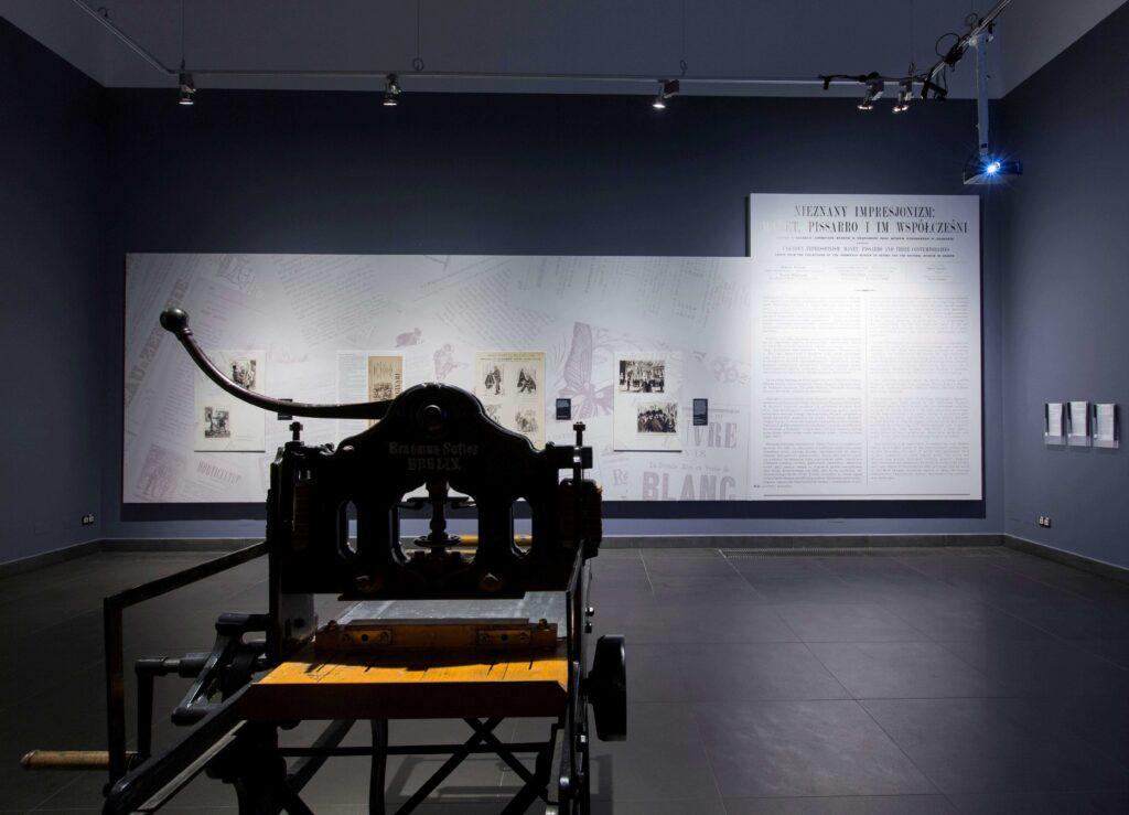 Fotografia przedstawia fragment aranżacji wystawy w przedsionku sali wystawowej. Stanowi ona wprowadzenie do wystaw. Na pierwszym planie znajduje się XIX-wieczna maszyna drukarska, w tle jest ciemna, szara ściana, na której umieszczony jest duży panel, pokryty jasną, beżową tapetą zrobioną za starych francuskich XIX wiecznych gazet. Na ich tle znajdują się mniejsze tablice z fragmentami stron gazet oraz tekstami komentarzy wprowadzającymi w tematykę wystawy.