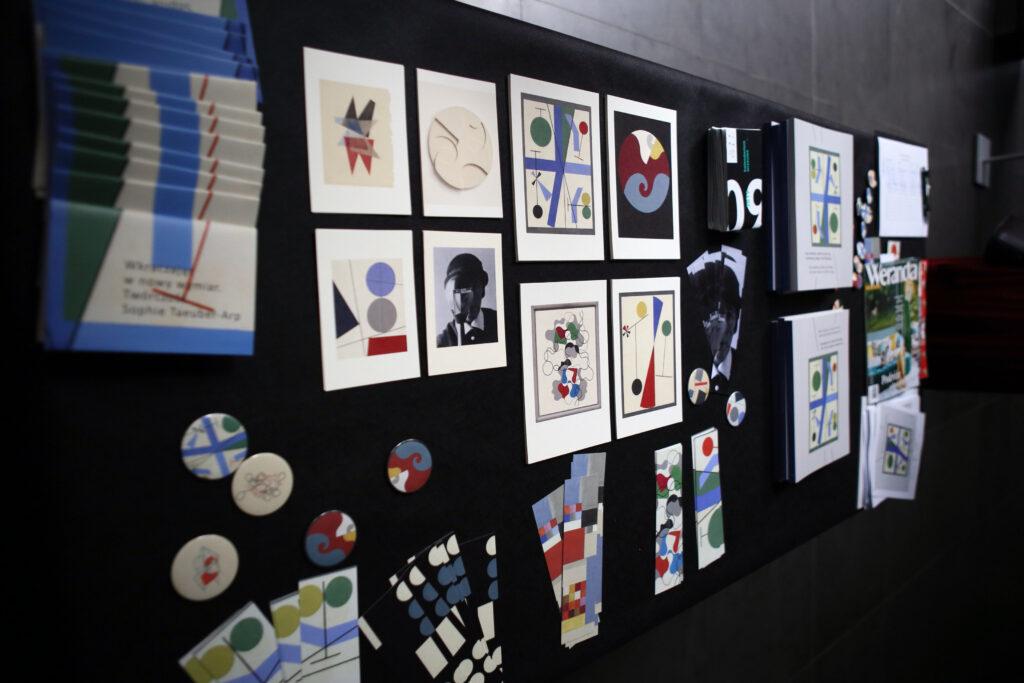Na zdjęciu widać ścianę pokrytą czarnym atłasem, na którym zawieszone zostały gadżety towarzyszące wystawie: okrągłe magnesy, pocztówki, zakładki do książek, katalogi, ulotki i kilka innych publikacji.