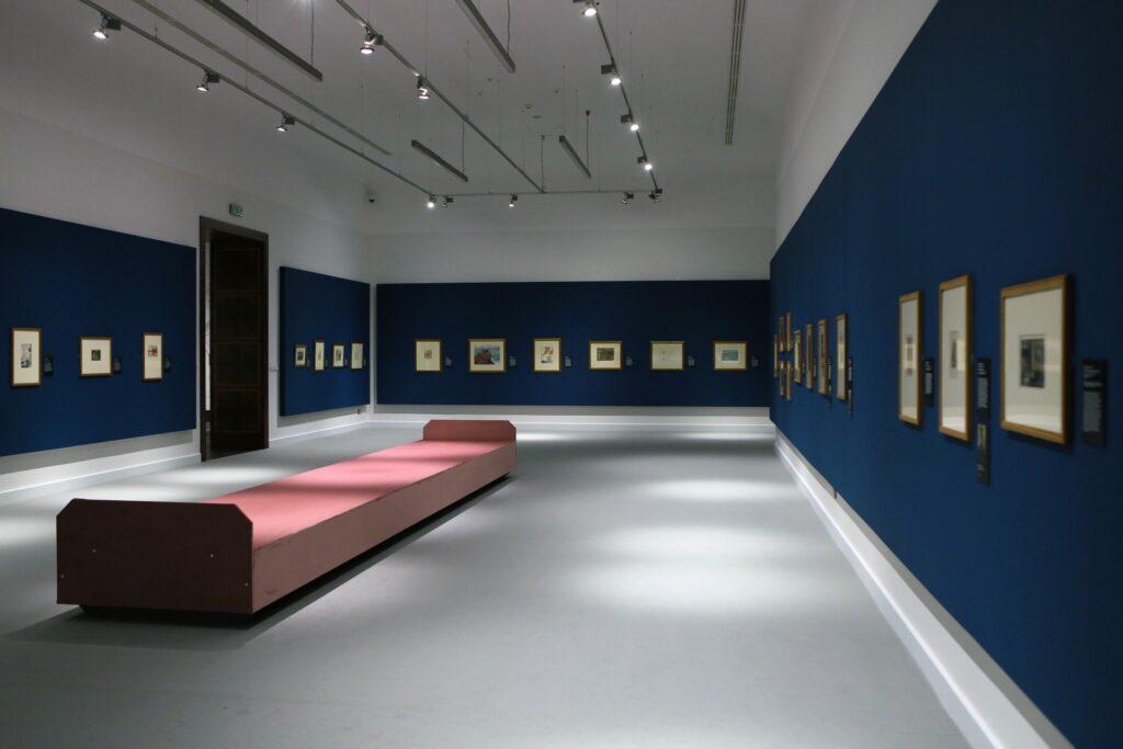 Fotografia przedstawia fragment aranżacji wystawy w Sali Wystaw. Ściany, na których zawieszone są oprawione w jasne, brązowe ramy grafiki są ciemnoniebieskie, podłoga jest jasnoszara. Na środku sali stoi duża, pokryta różową tkaniną ława, na której zwiedzający mogą usiąść. Na suficie sali widzimy szyny z lampami, oświetlającymi wystawę. Przy każdej pracy znajduje się czarna tabliczka, która zawiera opis danego obrazu.