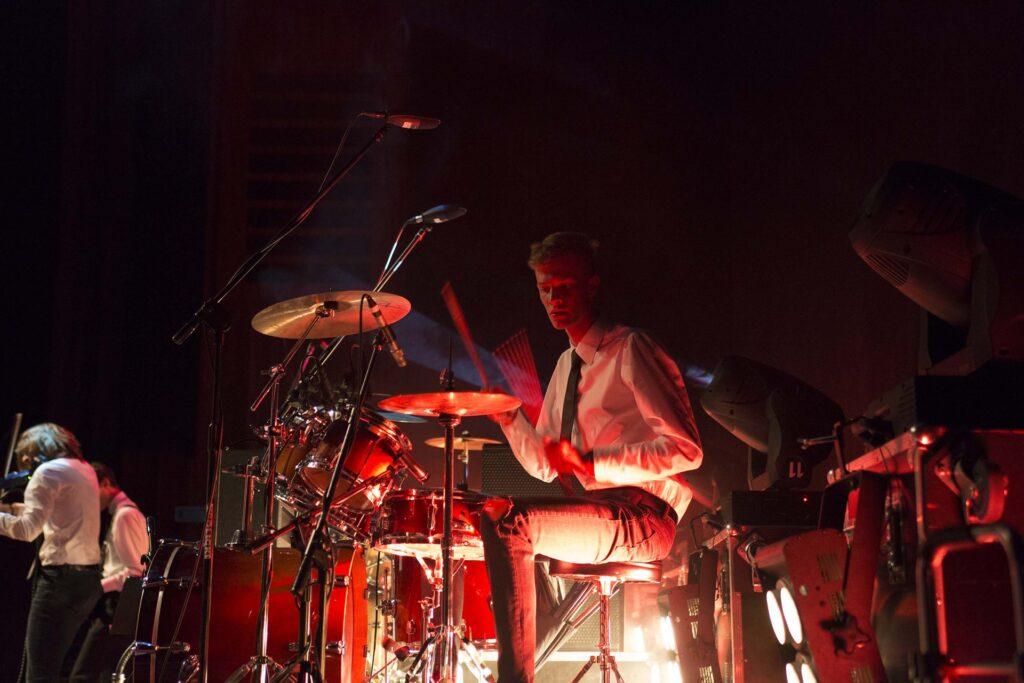 Zdjęcie z boku sceny. Na pierwszym planie widoczny jest perkusista podczas gry na talerzach. W tle po lewej widzimy niewyraźne sylwetki dwóch muzyków. Z przodu zdjęcia, z prawej strony przed perkusją stoją dwie duże lampy sceniczne.