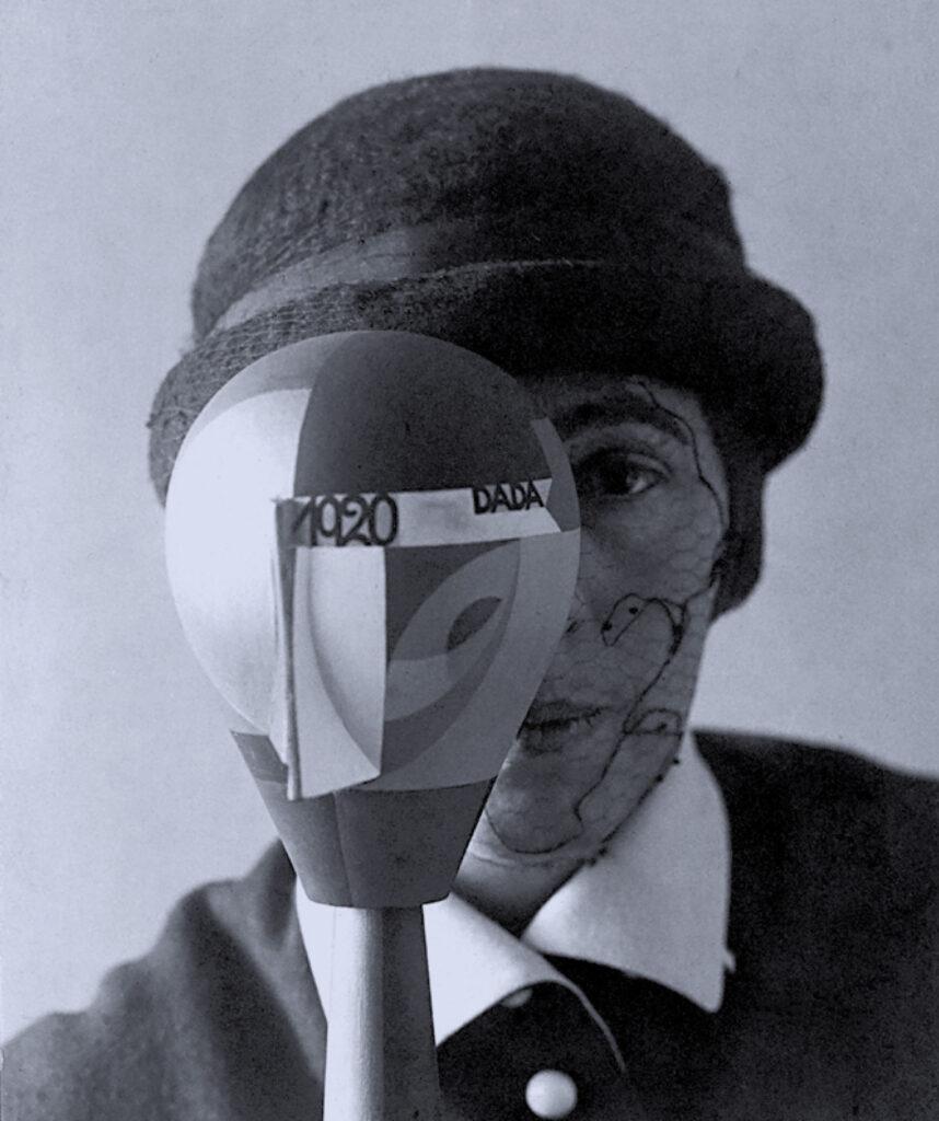 """Czarno-biała fotografia przedstawia artystkę w filcowym meloniku z twarzą zasłoniętą ażurową woalką. Kobieta patrzy na wprost, jednak pół twarzy ma zasłonięte przedmiotem przypominającym kształtem dużą żarówkę lub odwróconą gruszkę, pomalowaną w geometryczne figury z napisem 1920 DADA. Jest to dzieło artystki nazwane """"Głowa dada""""."""