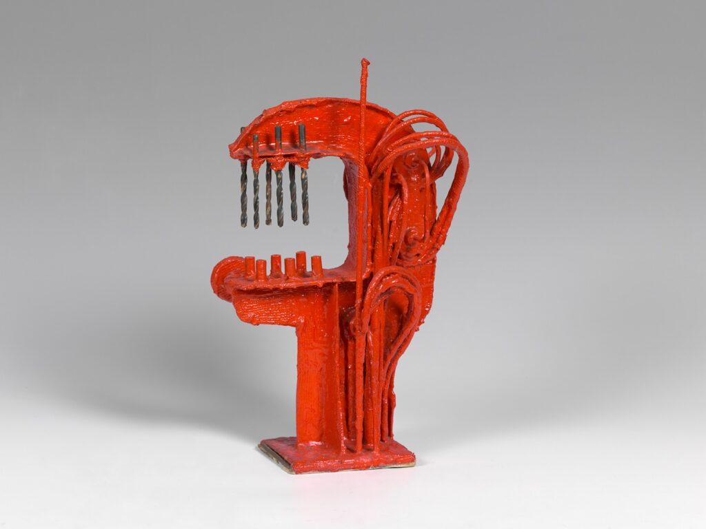 Na zdjęciu widzimy abstrakcyjną rzeźbę wykonaną z metalu i pomalowaną na czerwono, która kształtem przypomina głowę. Zamontowane w niej wiertła wyglądają jak długie zęby, a liczne druty jak włosy lub żyły. Interpretacja pracy może być zatem różna.