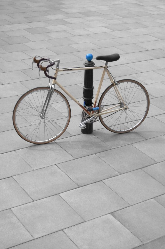 W części centralnej fotografii znajduje się rower kolarski, który przymocowany jest do czarnego, metalowego słupka miejskiego zakończonego niebieską kulą. Tłem zdjęcia są kwadratowe płyty chodnikowe w kolorze szarym.